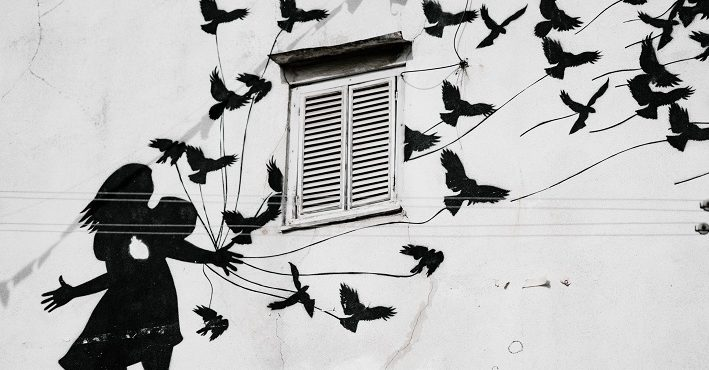 Mural of silhouette girl reaching out; birds flying upward