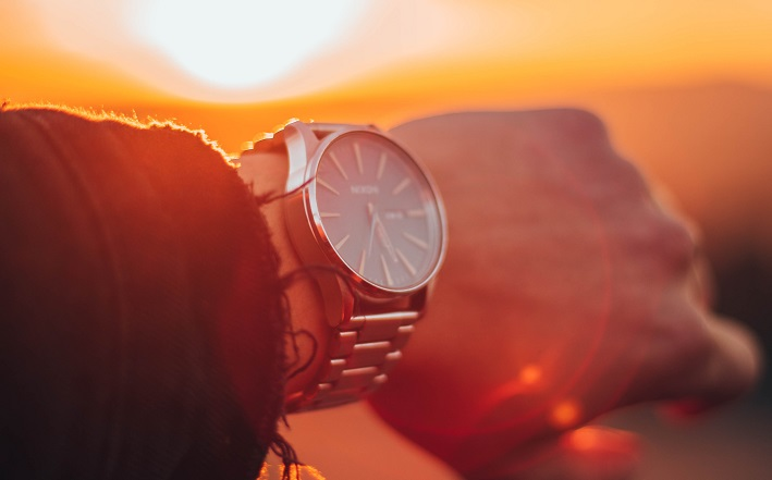 man wearing wristwatch in front of sunset