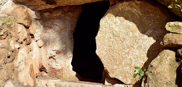round stone in obscuring tomb entry