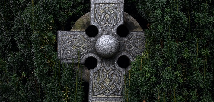 Celtic cross surrounded by evergreens