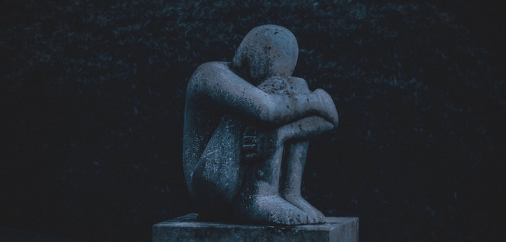 statue of person hugging knees