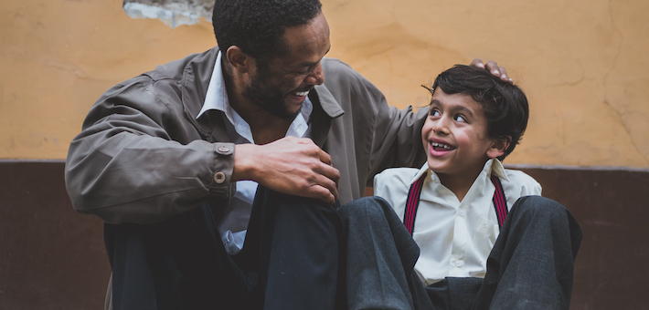 Man and boy smile at each other