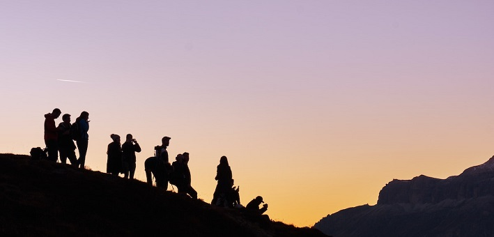 Silhouetted figures on hill at sunset