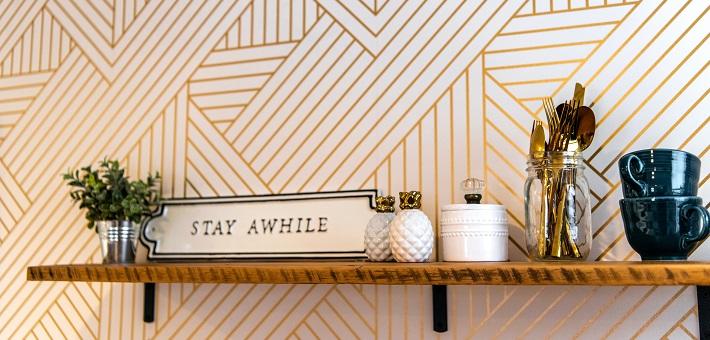Stay Awhile sign on bookshelf