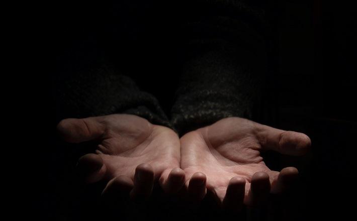 open hands on dark background