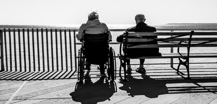 Elder adults sitting together on boardwalk