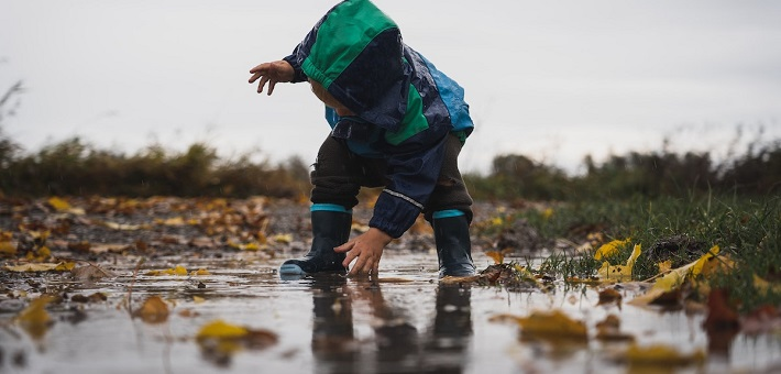 Toddler reaching hand into puddle