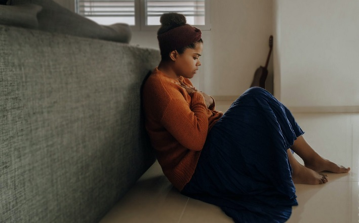 Woman sitting on floor in pain