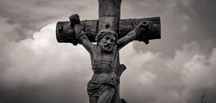 Stone crucifix against dark clouds