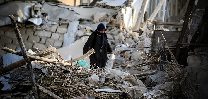 Figure standing amid rubble after earthquake