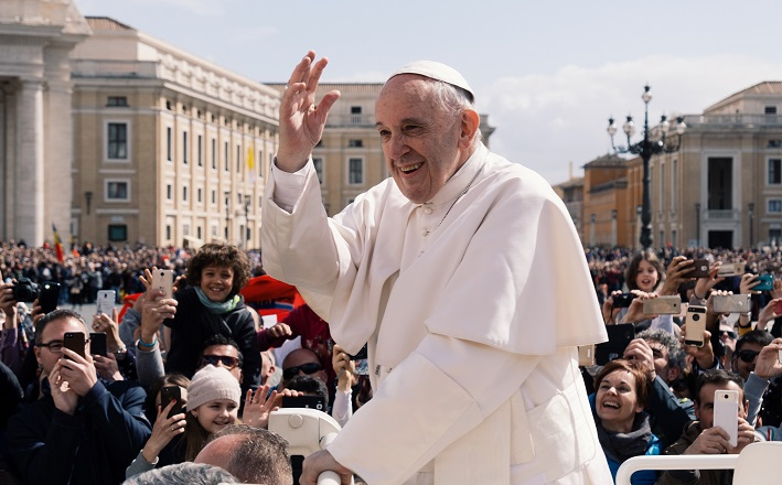 Pope Francis waves to crowd outdoors.